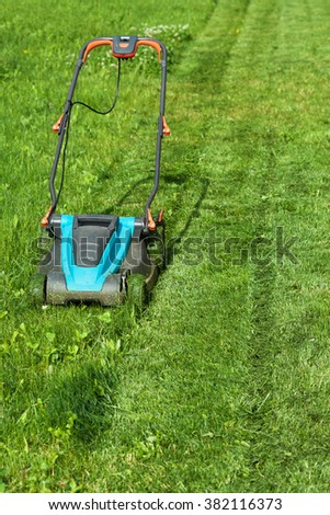 Freshly cut grass strips and blue lawnmower in summertime - copy space
