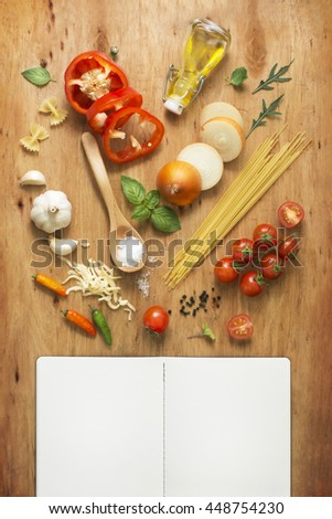 Freshly cut italian food spaghetti recipe ingredient and recipe book pages on wooden background. Flat lay overhead text space images. Recipe page text space images. - stock photo
