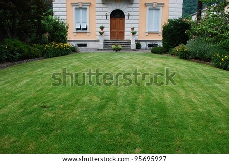 Freshly cut lawn in garden in front of a beautiful ancient villa, Italy