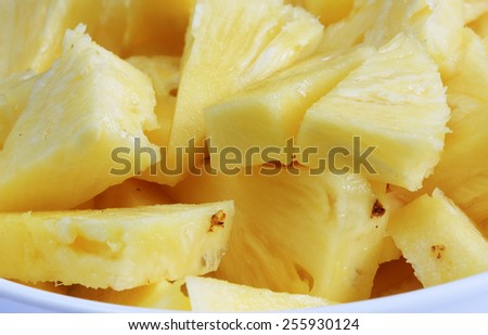 freshly cut pineapple pieces in a bowl - stock photo