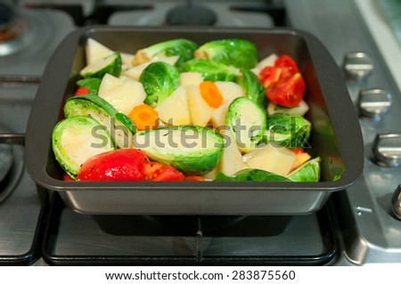 Freshly cut vegetables potatoes, tomatoes, carrot, brussels sprouts for a ragout, seasoned with salt, pepper and olive oil, in a pan to be cooked. Selective focus, focus on brussels sprout, copy space - stock photo