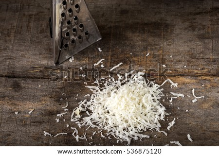 Freshly grated parmesan cheese on wooden table