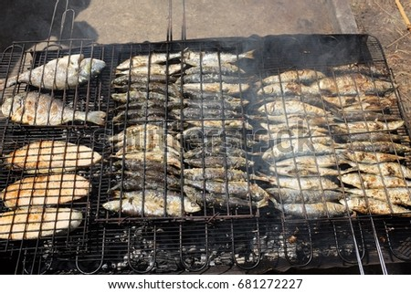 Freshly grilled sardines , salmon steak on the grill