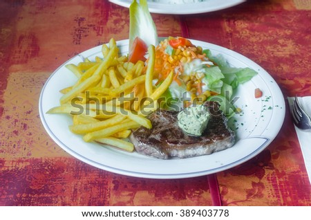 Freshly grilled steak with potatoes, french fries garlic butter and salad. - stock photo