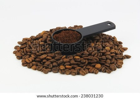 freshly ground black coffee in a spoon against a background of coffee grains - stock photo