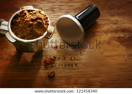 Freshly ground coffee beans in a metal filter on a wooden background with copyspace during preparation of a cup of aromatic filter coffee or espresso - stock photo