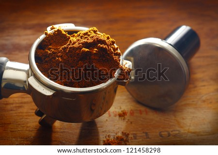 Freshly ground coffee overflowing over the rim of a metal filter onto a wooden surface with measuring spoon - stock photo