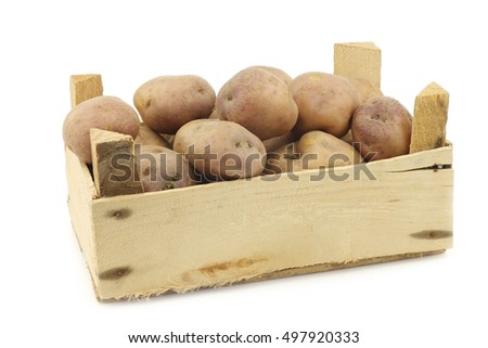"freshly harvested dutch potatoes called ""Koopmans Blue"" in a wooden crate on a white background"