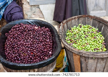 Freshly harvested green and black olives in a wooden basket for sale at Sineu market, Majorca, Spain