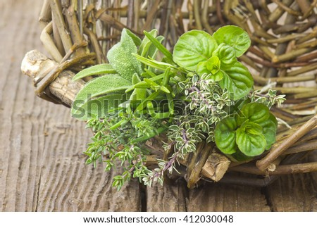 Freshly harvested herbs in a basket on wooden background