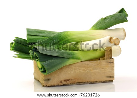 freshly  harvested leek in a wooden box on a white background - stock photo