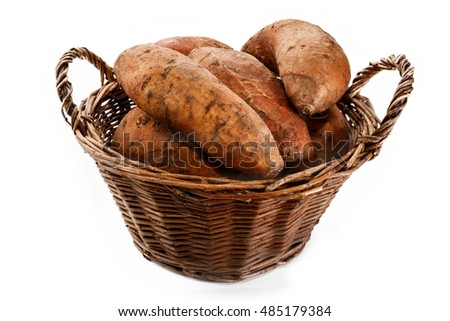 freshly harvested organic potatoes in a wicker basket isolated on white background