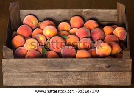Freshly harvested peaches in a wooden crate on a brown background - stock photo