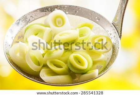 Freshly harvested sliced and cooked leeks served in a ladle for use in cooking as a flavoring for their pungent aromatic onion-like taste - stock photo