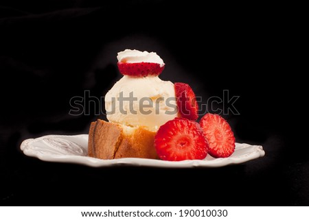 Freshly harvested strawberries piled up on a homemade fresh from the oven piece of pound cake topped with French vanilla ice cream - stock photo