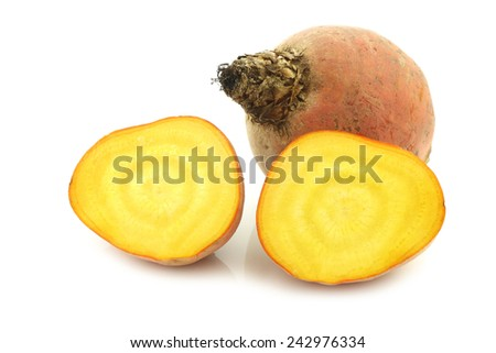 freshly harvested yellow beet and two halves on a white background - stock photo