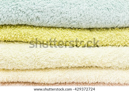freshly laundered bath towels stacked and folded in different colors  - stock photo