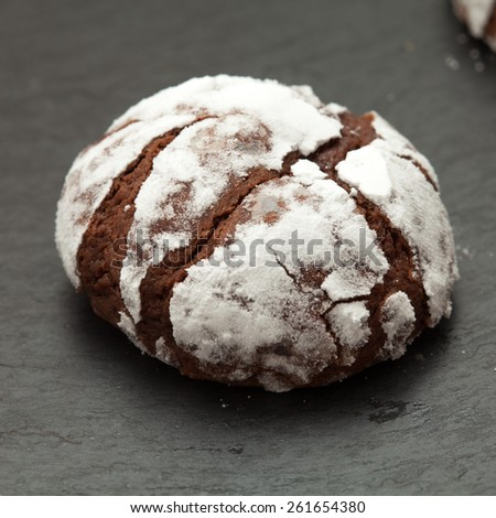 freshly made chocolate biscuits coated in icing sugar on a slate trivet - stock photo