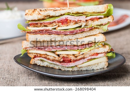 Freshly made club sandwiches served on black plate - stock photo
