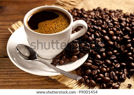 Freshly made coffee in a white cup surrounded by coffee beans on a wooden table. Fresh roasted coffee. - stock photo