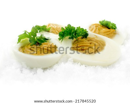 Freshly made deviled curried eggs buried in ice with garnish against a white background. Copy space. - stock photo