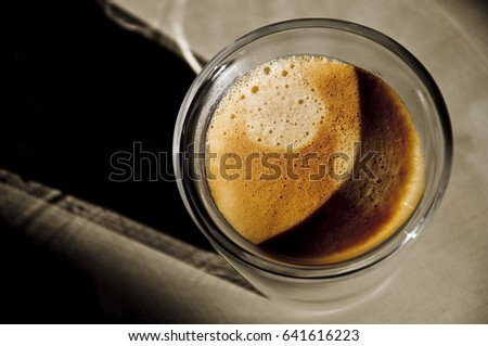 Freshly made espresso with beautiful crema, beautiful shadow and lighting through the cup. Perspective 1.