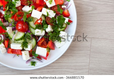 Freshly made Greek salad with vine ripened tomatoes and cubes of feta cheese. Served in a white bowl with cucumber and herbs. - stock photo