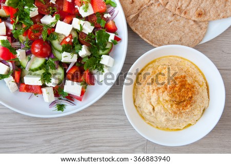 Freshly made Greek salad with vine ripened tomatoes and cubes of feta cheese. Served with home made hummus in white bowls with pita flat bread. - stock photo