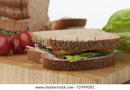 Freshly made ham salad sandwich on chopping board with loaf and vegetables
