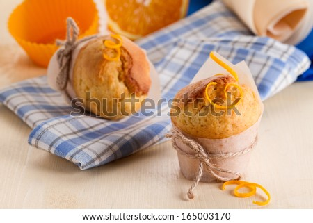 Freshly made orange muffins on kitchen table - stock photo