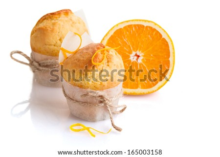 Freshly made orange muffins on the white background - stock photo