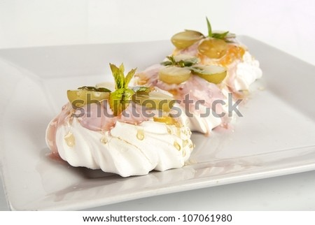 Freshly made pavlova with mint against white