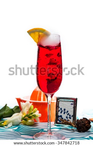 Freshly made red cocktail with a slice of lemon