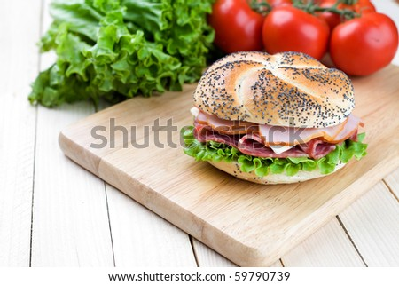 Freshly made sanwich on wooden cutting board - stock photo