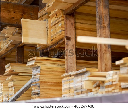 Freshly milled wood stacked on shelves in a lumber yard ready for sale. - stock photo