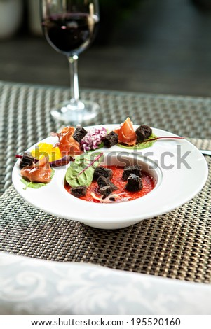 Freshly mixed gazpacho in white plate with a glass of wine, served outdoors