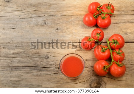 freshly organic harvested and wet tomatoes and juice on a rustic, wooden kitchen table - stock photo