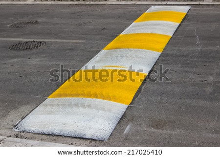 Freshly painted speed bump for slowing traffic near school. Selective focus. - stock photo