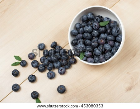Freshly picked blueberries. Blueberries with green leaves on wooden background. Blueberry antioxidant. Concept for healthy eating and nutrition