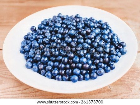 Freshly picked blueberries on a plate - stock photo