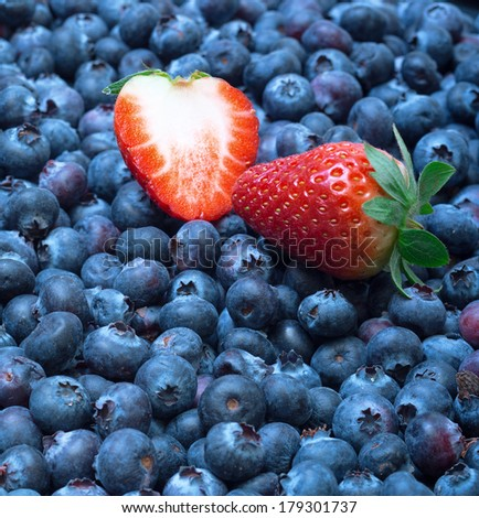 Freshly picked blueberries with strawberry, closeup background