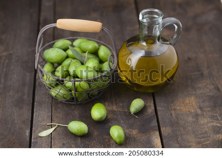 Freshly picked green olives and olive oil in jar on wooden table - stock photo