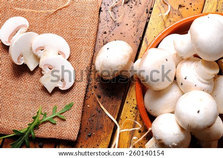 freshly picked mushrooms on a wooden table in the field prepared for cooking top view - stock photo