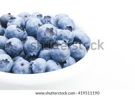 Freshly picked organic blueberries in white bowl - close up shot with focus on berries - stock photo