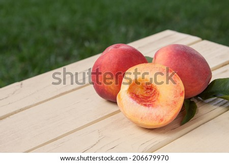 Freshly picked organic peaches with leaves from tree - stock photo