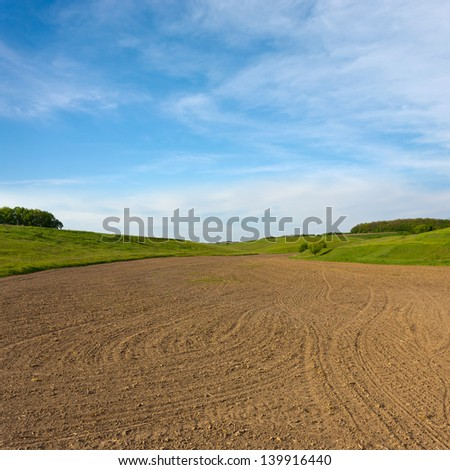 freshly ploughed field in spring before the sead among green meadow