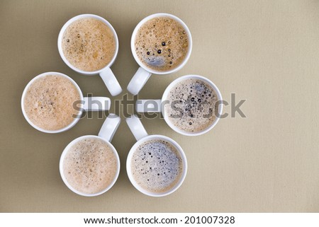 Freshly poured coffee topped with frothy bubbles arranged in a circular radiating design with converging handles on a beige background with copyspace, overhead view - stock photo