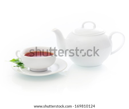 Freshly poured cup of hot tea with a teapot in an elegant white design standing on a white background with copyspace - stock photo