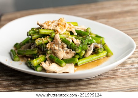 Freshly prepared Asian style chicken and asparagus stir fry with garlic. - stock photo