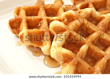 Freshly prepared belgian waffles with maple syrup on cream colored serving plate.  Macro with shallow dof. - stock photo